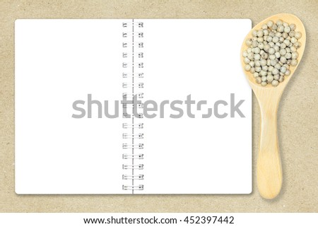 White pepper in wooden spoon and notebook paper on recycled brown paper background for design with copy space for text or image. - stock photo