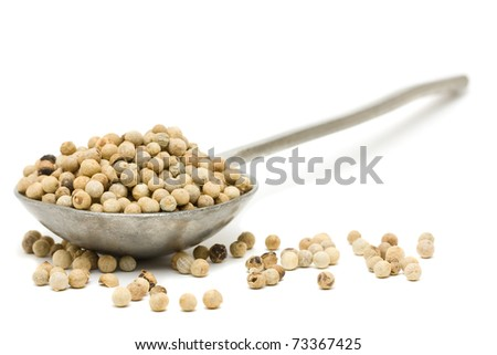 White peppercorns on metal spoon over white background - stock photo