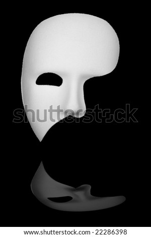 White phantom of the opera half face mask isolated on black background