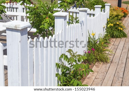 White picket fence along a wooden sidewalk. - stock photo