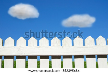 White picket fence, green grass and blue sky - stock photo