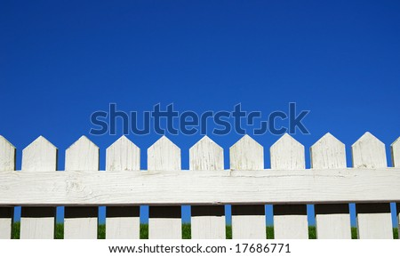 White picket fence, green grass and sky - stock photo