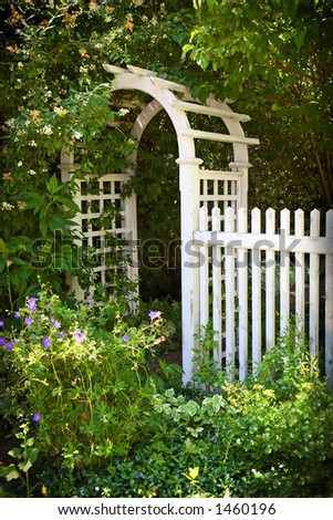 White picket fence with arch in a garden. - stock photo