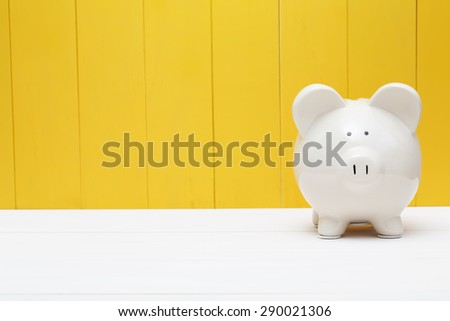 White piggy bank against a yellow wooden wall - stock photo