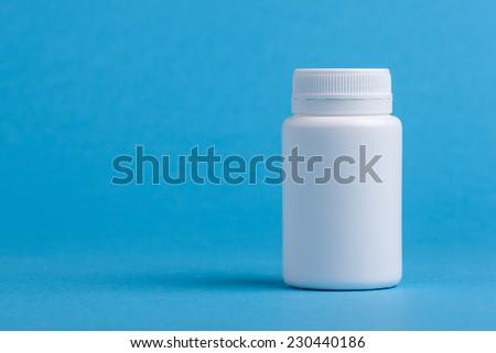 White pill bottle against blue background. - stock photo