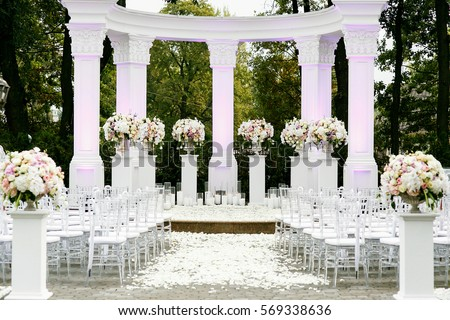 white pillars with bouquets of roses surround place prepared for wedding ceremony