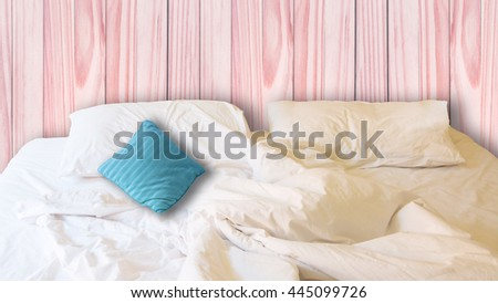 white pillow and blue pillow on bed and with wrinkle messy blanket in red vintage bedroom, from sleeping in a long night. - stock photo