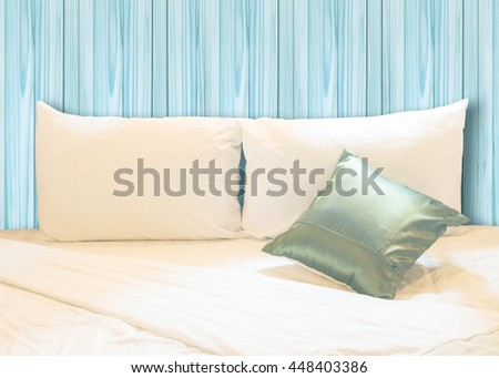 white pillow and green pillow on bed and with wrinkle messy blanket in vintage wooden bedroom, from sleeping in a long night. - stock photo