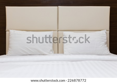 white pillow and leather headboard in bedroom - stock photo