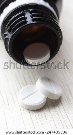 White pills and bottle on table. Pills spilling from container. Copy space. Slightly defocused and closeup shot. - stock photo
