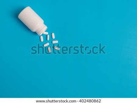 white pills and pill bottle on blue sky background.
