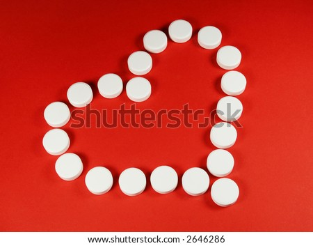White pills forming a heart shape, on red. - stock photo
