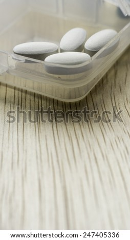White pills in transparent plastic container on wooden surface. Copy space. Slightly defocused and closeup shot. - stock photo