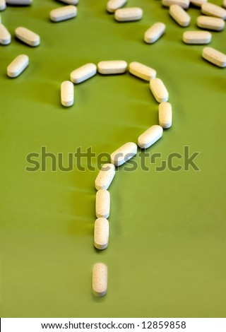 White pills on green background as a question mark, to eat or not to eat - stock photo