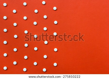 White pills on orange background with copy space.Useful as background for medicine, pharmacy, prescription, homeopathy - stock photo