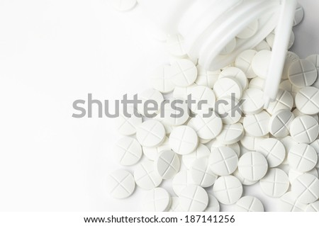 white pills out of pill bottle with copy space - stock photo