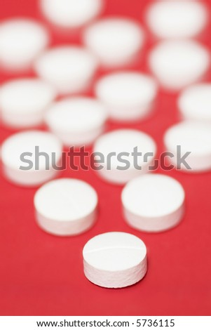 White Pills Over Red Background, Close-Up Shot, Focus On Front