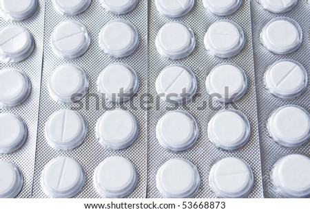 White pills packed in tin blisters