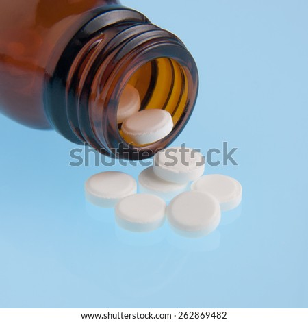 White pills poured out of bottle - stock photo