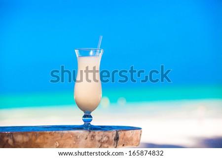 White pina colada on the beach table - stock photo