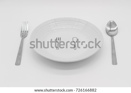White plain with fork and spoon design on it between fork and spoon