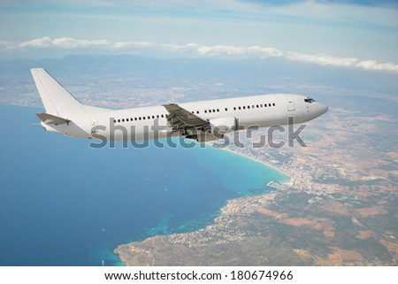 White plane in flight with island Mallorca in background - stock photo