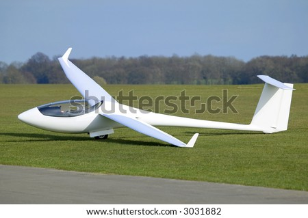 White Plane or Glider at rest on an airfield - stock photo
