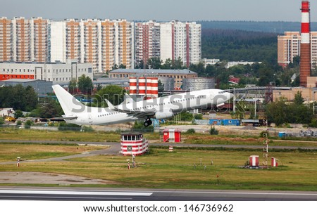 white plane takes off from the runway on the background of houses - stock photo