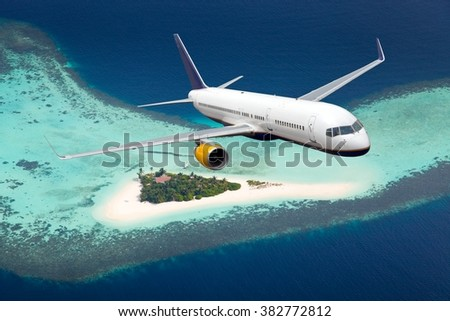 White plane with blue Tail. Aircraft flies over ocean and tropical (Maldives) island. - stock photo
