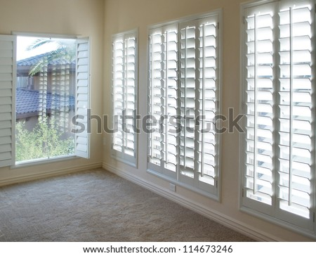 White plantation style wood Shutters for luxury Interior Design in condo. - stock photo