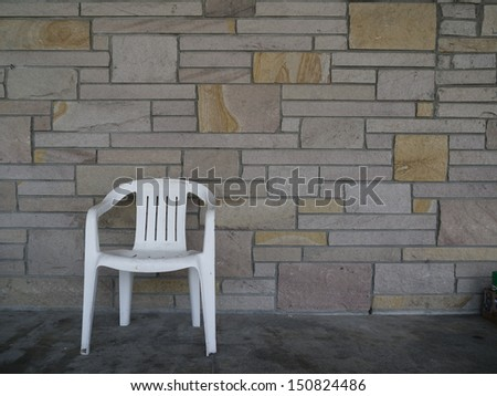 white, plastic chair in front of irregular shaped bricks wall; neutral colors