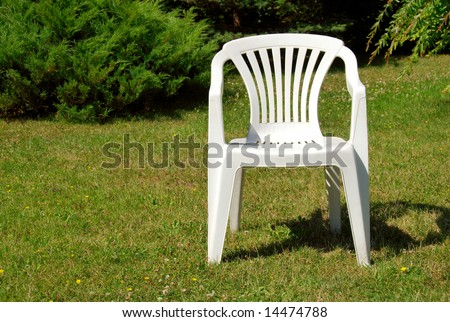 White plastic chair on the grass in the garden - stock photo
