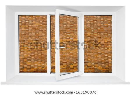 White plastic cutout triple door window with brick wall inside - stock photo