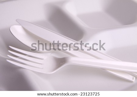 White plastic eating utensils on a white foam disposable plate with partitions. - stock photo