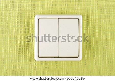 White plastic electricity switch on the green wall - stock photo