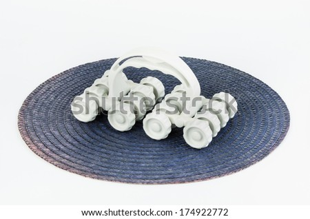 White plastic massager with wheels on blue mat isolated on white background - stock photo