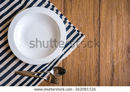white plate and fork on old wooden table with checked tablecloth and copy space good - stock photo