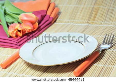 White plate and orange covers - stock photo