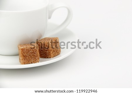White plate and white coffee cup with brown sugar