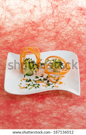 White plate decorated with carving of yellow turnip and zucchini, red ceiling structure as background / Plate decorated with carving of crops - stock photo