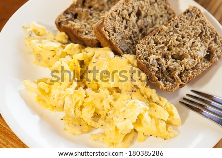 White plate filled with scrambled eggs and banana bread - stock photo