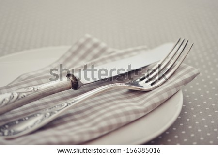 White plate, fork and knife on light polka dot background.