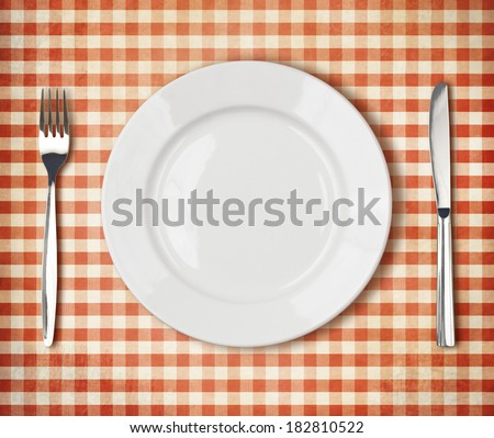 white plate, fork, knife top view over old red picnic tablecloth - stock photo