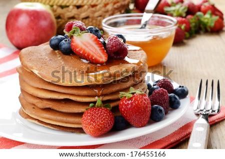 White plate full of pancakes with strawberries raspberries blueberries and honey - stock photo