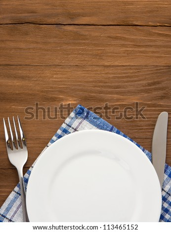 white plate, knife and fork at napkin on wooden background - stock photo