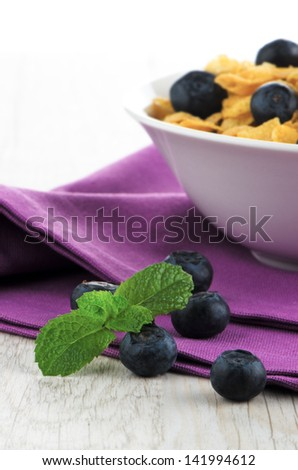 White plate of corn cereal and blueberries for healthy breakfast.