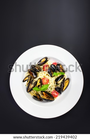 White plate of italian pasta with mussels, cherry tomato  and herbs for a tasty seafood meal closeup over blackboard with copyspace - stock photo