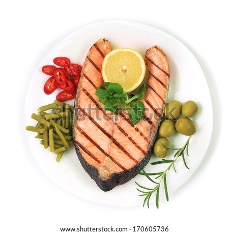 White plate of salmon steak with vegetables. - stock photo