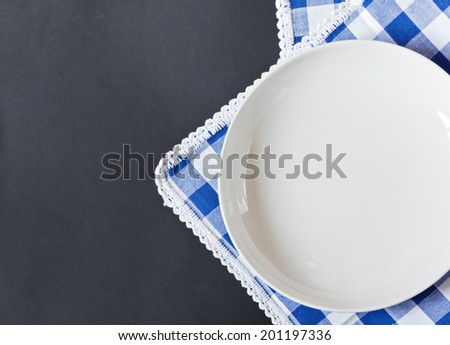 White plate on a blue checkered napkin and black background for your text