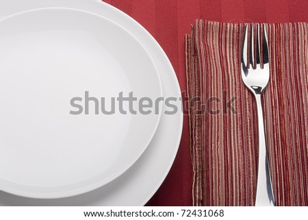 White plate on a red background with a red cloth.